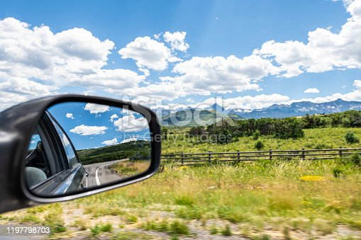 istock Wide angle view near Ouray, Colorado highway scenic road 550 San Juan rocky mountains range with Ridgway countryside rural fence and rear view mirror 1197798703