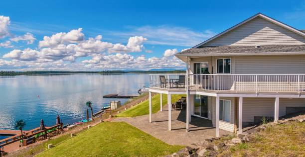 Wide angle view of a beautiful, large modern luxury summer holiday home, featuring sun decks, glass railings and large windows, set beside a freshwater lake in central British Columbia, Canada. A large two-story house with beige vinyl siding, a shingled roof, a large outdoor deck and patio, with outdoor furniture situated on a freshwater lake. There is a a dock with a sitting area and equipment for water sports. promenade stock pictures, royalty-free photos & images