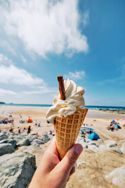 POV wide angle view of a hand holding Ice cream cone at Fistral Beach, Newquay on a sunny June day. stock photo