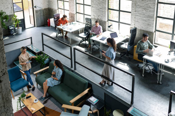 Wide Angle View of a Modern Loft Open Space Office With Businesspeople Working in It Group of young entrepreneurs/ freelancers working at a spacious open space office. coworking stock pictures, royalty-free photos & images