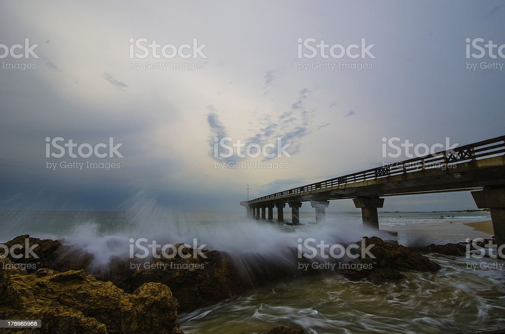 Wide angle view of a pier with crashing waves stock photo