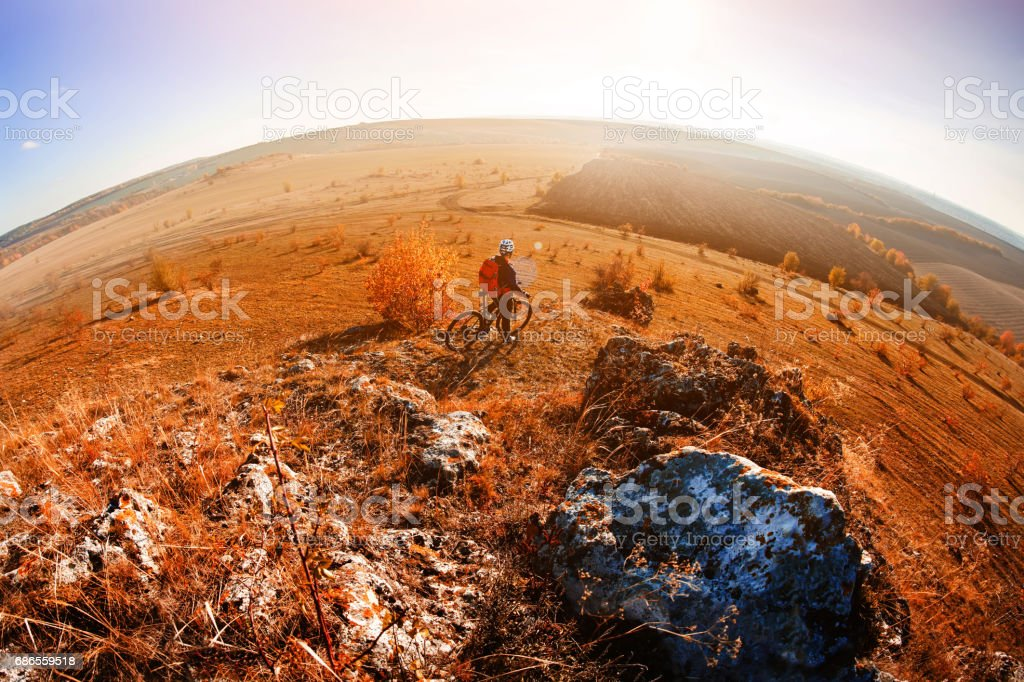 Wide angle view of cyclist standing with mountain bike on trail at sunset royaltyfri bildbanksbilder