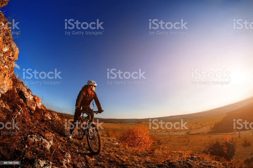 Wide angle view of cyclist standing with mountain bike on trail at sunrise Lizenzfreies stock-foto