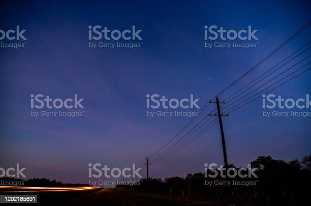 Photo of Wide Angle View of Early Sunrise On Country Road Road With Stars Visible in the Sky
