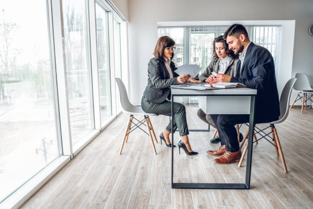 Wide angle view of group business people in bright spacious modern office near panoramic windows. Young businessman and businesswoman sitting at the desk in design studio with mature woman sales manager. Work with client concept stock photo