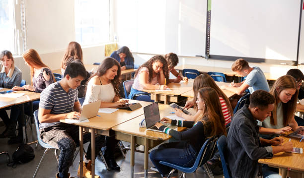 Wide Angle View Of High School Students Sitting At Desks In Classroom Using Laptops Wide Angle View Of High School Students Sitting At Desks In Classroom Using Laptops monkeybusinessimages stock pictures, royalty-free photos & images