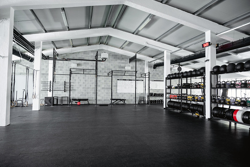 Spacious and unoccupied workout facility with exposed ceiling and medicine balls, kettlebells, and weights on shelves.