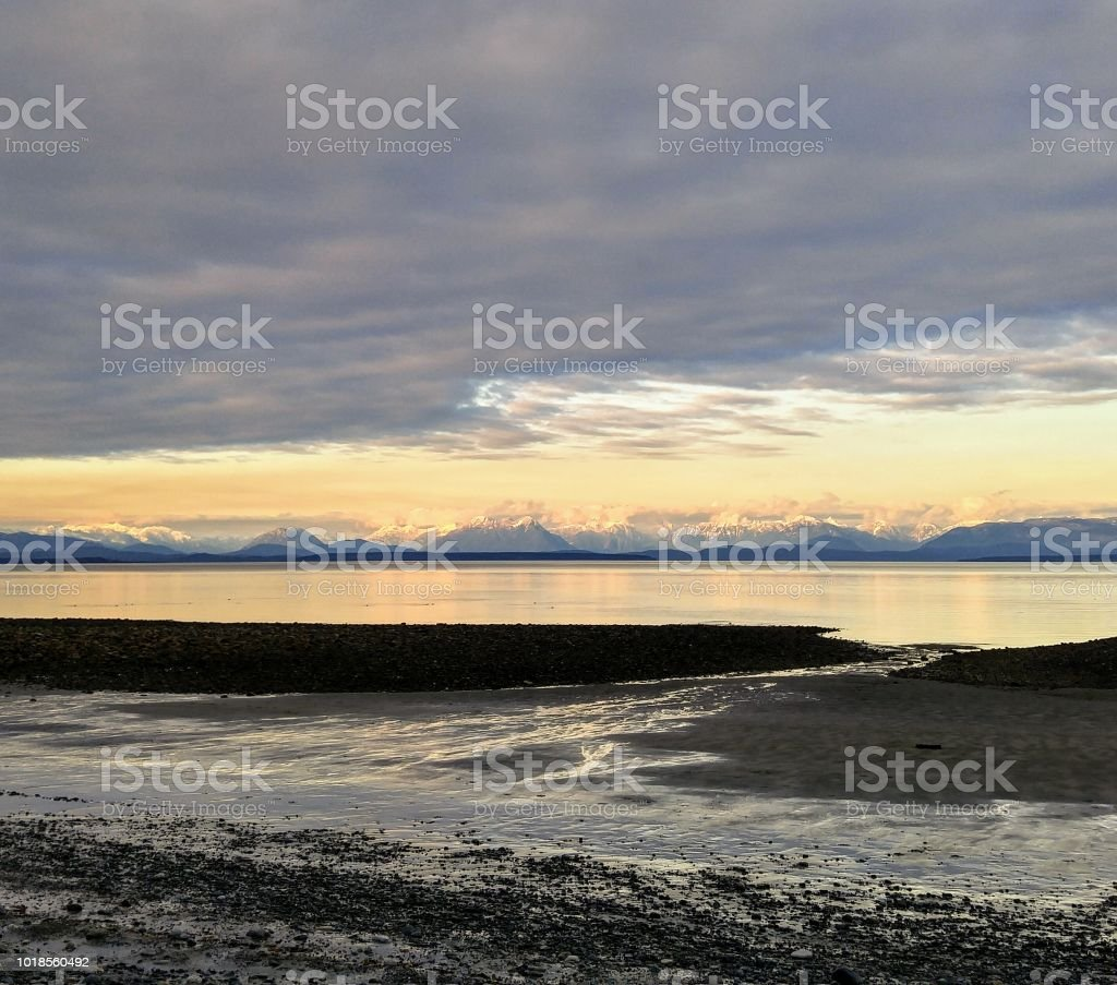A wide angle view of the coastal mountains in spring at low tide stock photo