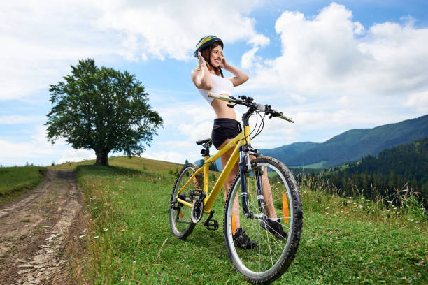 Wide angle view of young happy girl biker riding on yellow bicycle on a rural trail in the mountains, wearing helmet. Mountains, big tree and cloudy sky on the background. Outdoor sport activity Wide angle view of young happy girl biker riding on yellow bicycle on a rural trail in the mountains, wearing helmet. Mountains, big tree and cloudy sky on the background. Outdoor sport activity female biker resting stock pictures, royalty-free photos & images