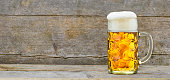 wide angle view to big glass filled with Bavarian lager beer on wooden plank with copy space