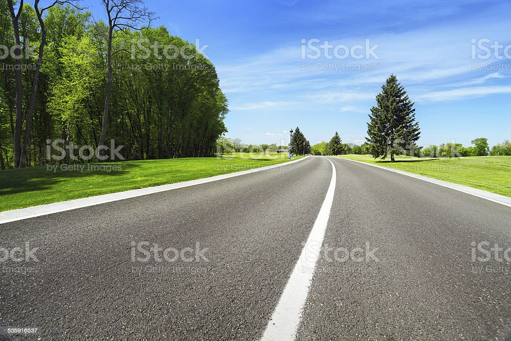 Wide asphalt road and green trees stock photo