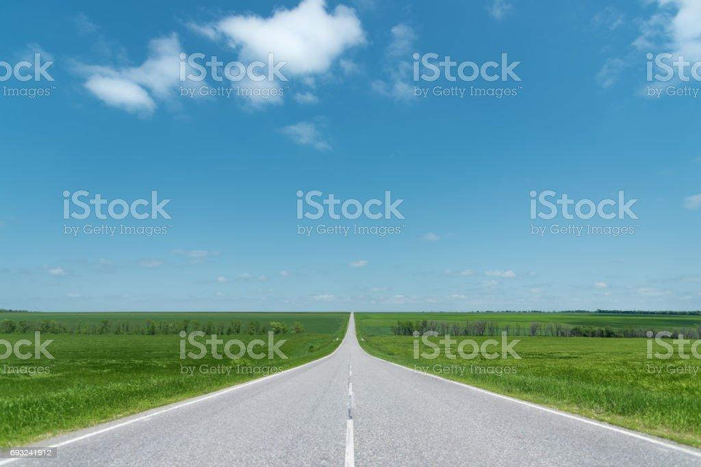 A wide asphalt road between green fields stock photo