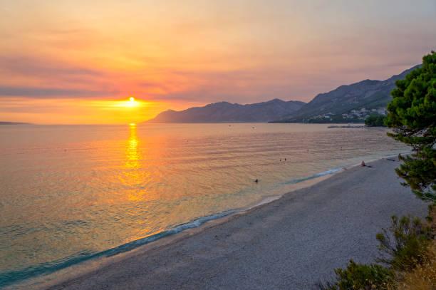Wide beach in Baška Voda at sunset, Makarska Riviera, Croatia stock photo
