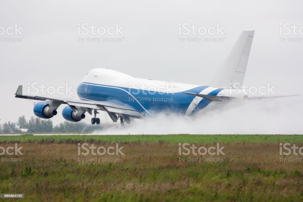 Wide body cargo airplane takes off in a heavy rain leaving behind a cloud of splatter стоковое фото