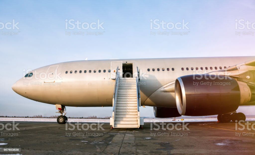 Wide body passenger airplane with a boarding stairs at the airport apron in the evening sun стоковое фото