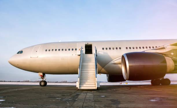Widebody Passagierflugzeug mit einem Internaten Treppen auf dem Flughafen-Vorfeld in der Abendsonne – Foto