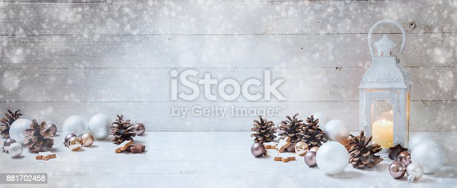 istock wide christmas background with a candle light lantern, baubles, cinnamon stars and cones on rustic white wood, panorama format for website banner, copy space 881702458
