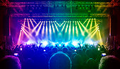 Wide concert arena with lit stage and crowd clapping