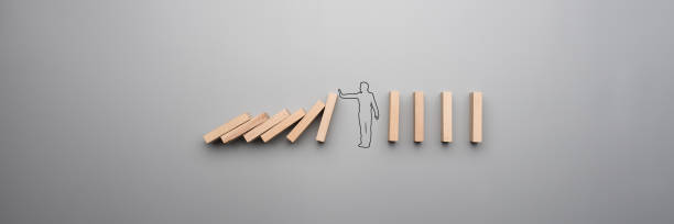 Wide cropped image of the outline of a businessman stopping the domino stock photo