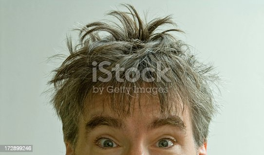 Wide eyed male with bed head on a white background.