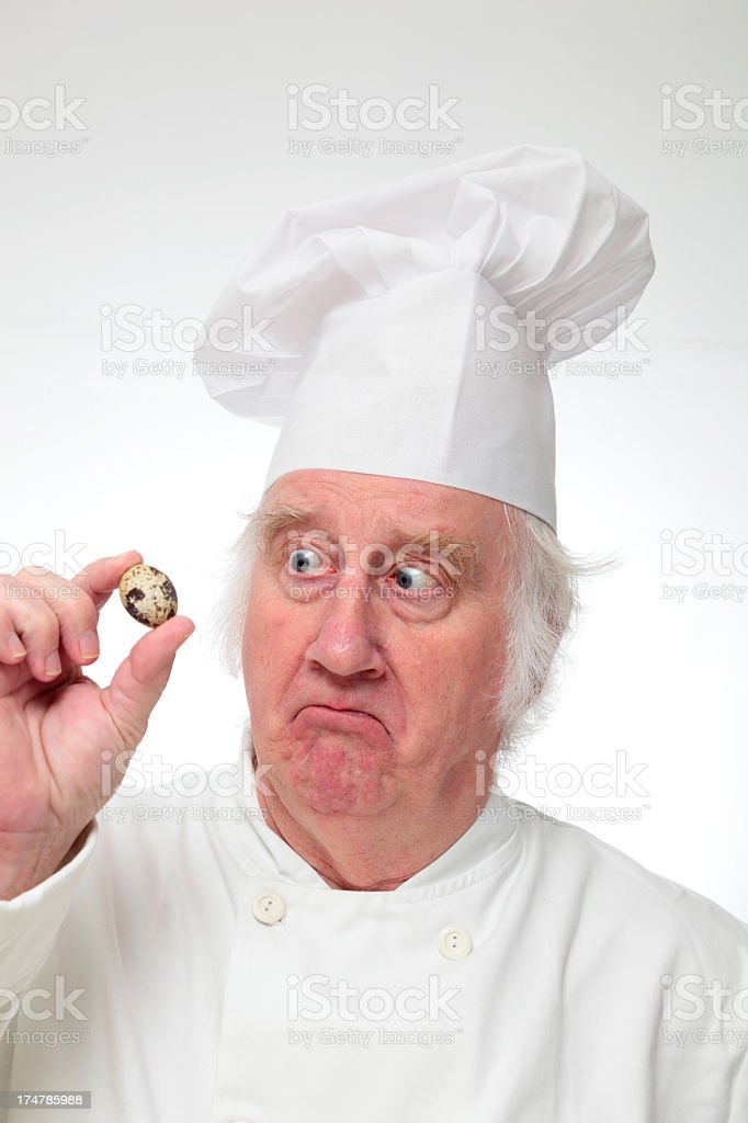 wide eyes chef with quails egg puzzled on plain background royalty-free stock photo