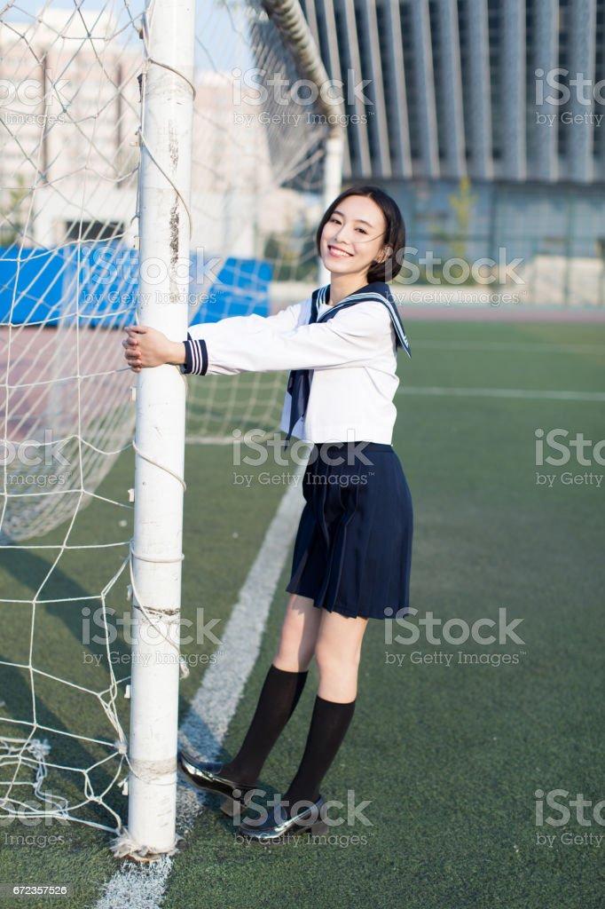 geniş futbol alan orada güzel bir Çinli kız öğrenci stok fotoğrafı