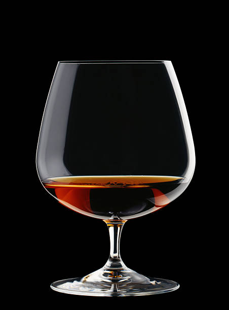 a wide glass of brandy isolated on a black background - 干邑 白蘭地 個照片及圖片檔