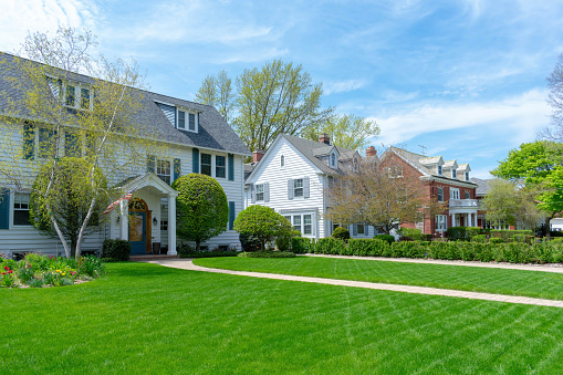 istock Wide green front lawns in traditional suburban residential neighborhood 1141528775