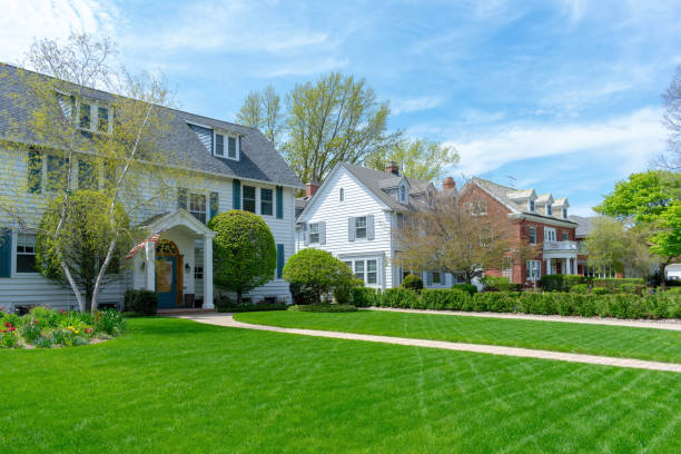 Wide green front lawns in traditional suburban residential neighborhood Row of traditional suburban homes and front lawns in nice neighborhood colonial style stock pictures, royalty-free photos & images