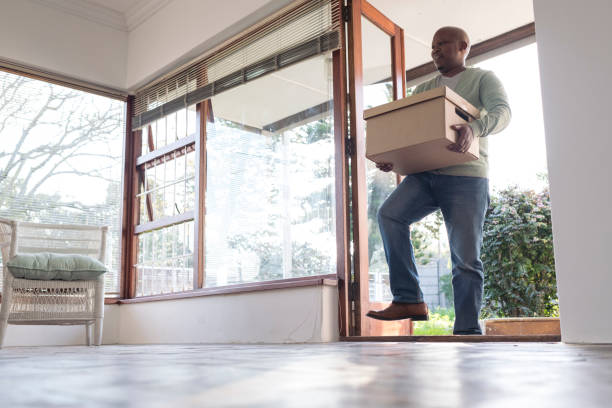 Wide low angle father carries boxes into new house stock photo