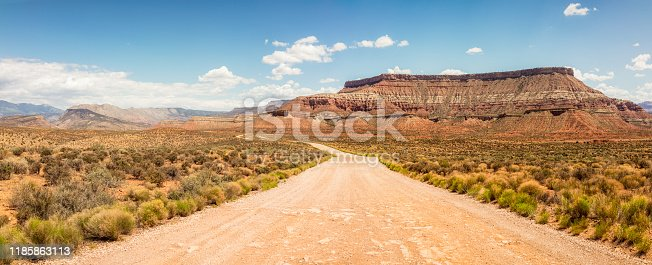 Rock formations surrounding a winding dirt road in southern Utah, USA.