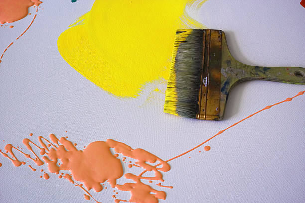 Wide Paintbrush Yellow And Orange Paints On The Canvas stock photo