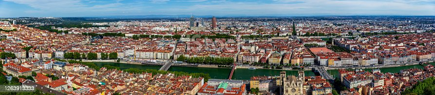 Wide panorama aerial view of Lyon cityscape with Saone and Rhone river, La Part-Dieu business district skyscrapers and buildings in background and hostoric monuments like St Jean Cathedral from Vieux Lyon district. Photo taken in Lyon famous city, Unesco World Heritage Site, in Rhone department, Auvergne-Rhone-Alpes region in France, Europe during a sunny summer day.
