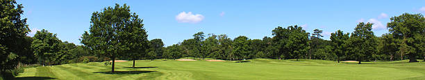Wide panorama image of golf course, bunkers, trees, blue sky stock photo