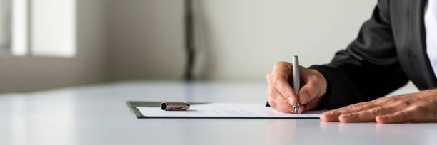 Wide panorama view of businessman hand signing legal or insurance document stock photo