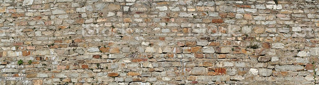 Wide photograph of a stone wall isolated on black stock photo