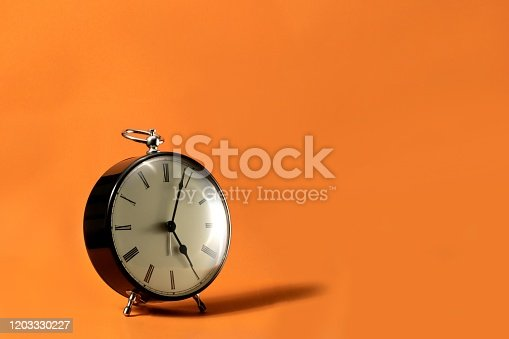 816405814 istock photo A wide portrait of a small old fashioned antique alarm clock with roman numbers on the dial on an orange background. The hands of the clock are pointing at a little past 5 o'clock. 1203330227