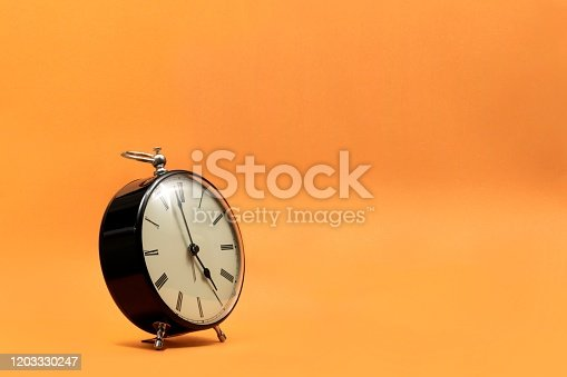 816405814 istock photo A wide portrait of a small old fashioned antique alarm clock with roman numbers on the dial on an orange background. The hands of the clock are almost pointing to 5 o'clock. 1203330247