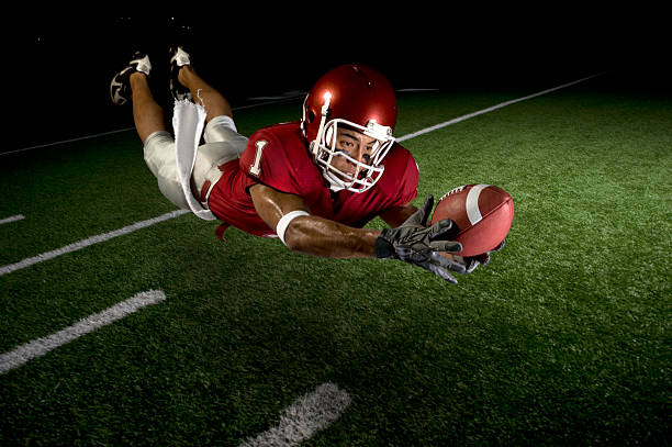 Wide Receiver Making a Diving Catch African-American football wide receiver diving to make a catch. Horizontally framed shot. catching stock pictures, royalty-free photos & images