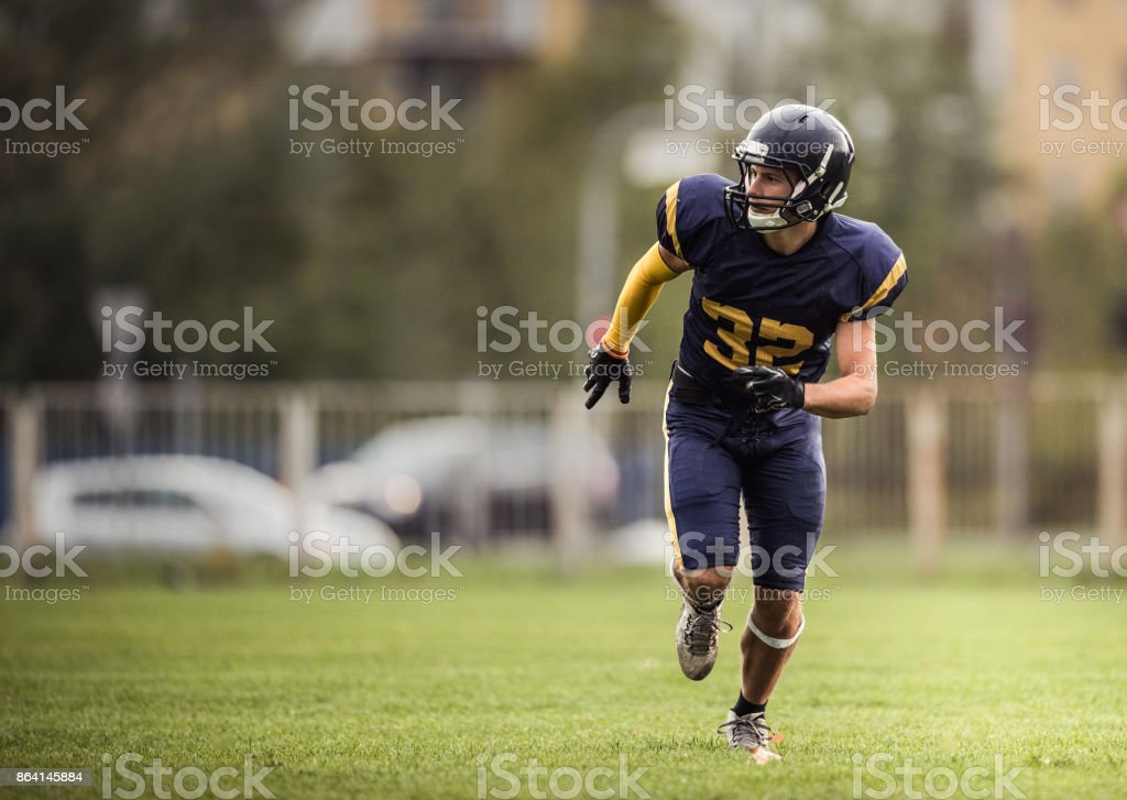 Wide reciver running on a playing field during American football match. royalty-free stock photo