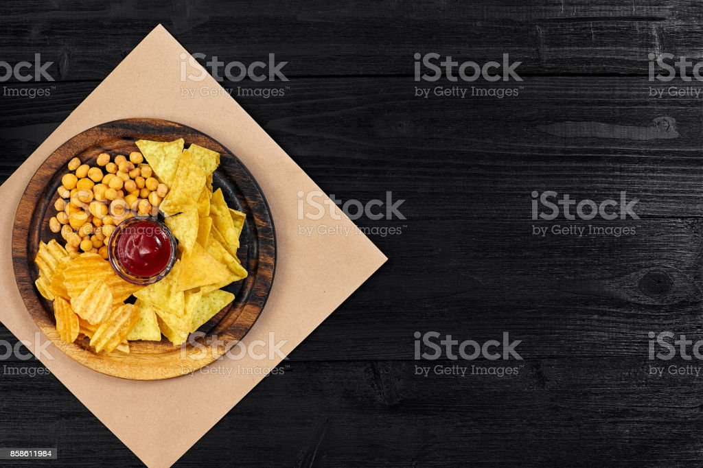 Wide selection of snacks for beer with different sauces on parchment top view stock photo