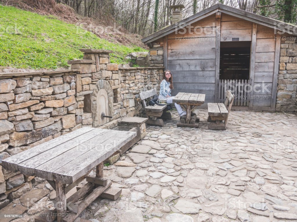Pleasing Wide Shot Of A Girl Tourist Sitting Outdoors On Old Wooden Bench And Table And Resting Stock Photo Download Image Now Ocoug Best Dining Table And Chair Ideas Images Ocougorg