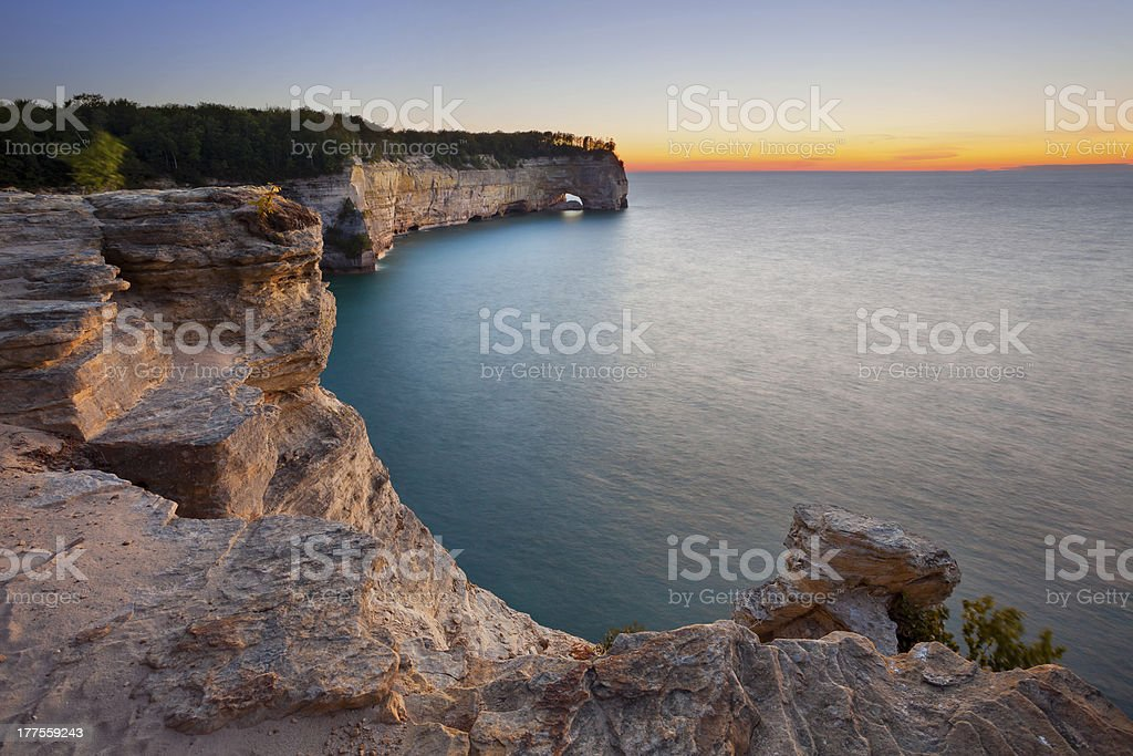 Wide shot of rocks looking over sea at sunset in Michigan stock photo