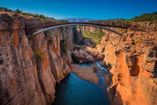 A wide shot of the river gorge and a high bridge at Bourke's Luck Potholes in Mpumalanga, South Africa stock photo
