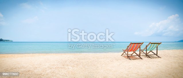 istock Wide shot of two deckchairs facing out to sea on idyllic beach. 996272632