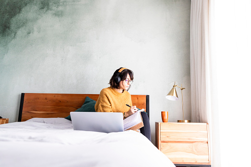 Wide shot woman taking notes while in video conference working in bedroom