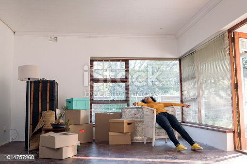 Young woman lies relaxing in a chair taking a break from moving in to her new house, boxes, pot plants and furniture around her.