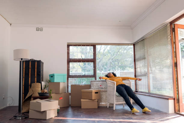 Wide shot young woman lies relaxing in a chair taking a break from moving in to her new house stock photo