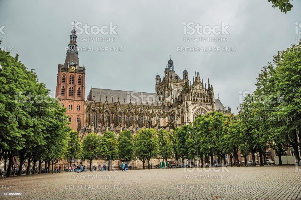 Breed plein met kasseien en bomen voor St. John's kathedraal in een bewolkte dag bij s-Hertogenbosch. foto