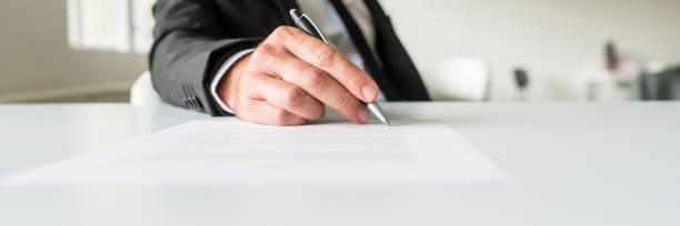 Breites Bild des Geschäftsmannes, der an seinem Schreibtisch sitzt und ein Dokument unterschreibt – Foto